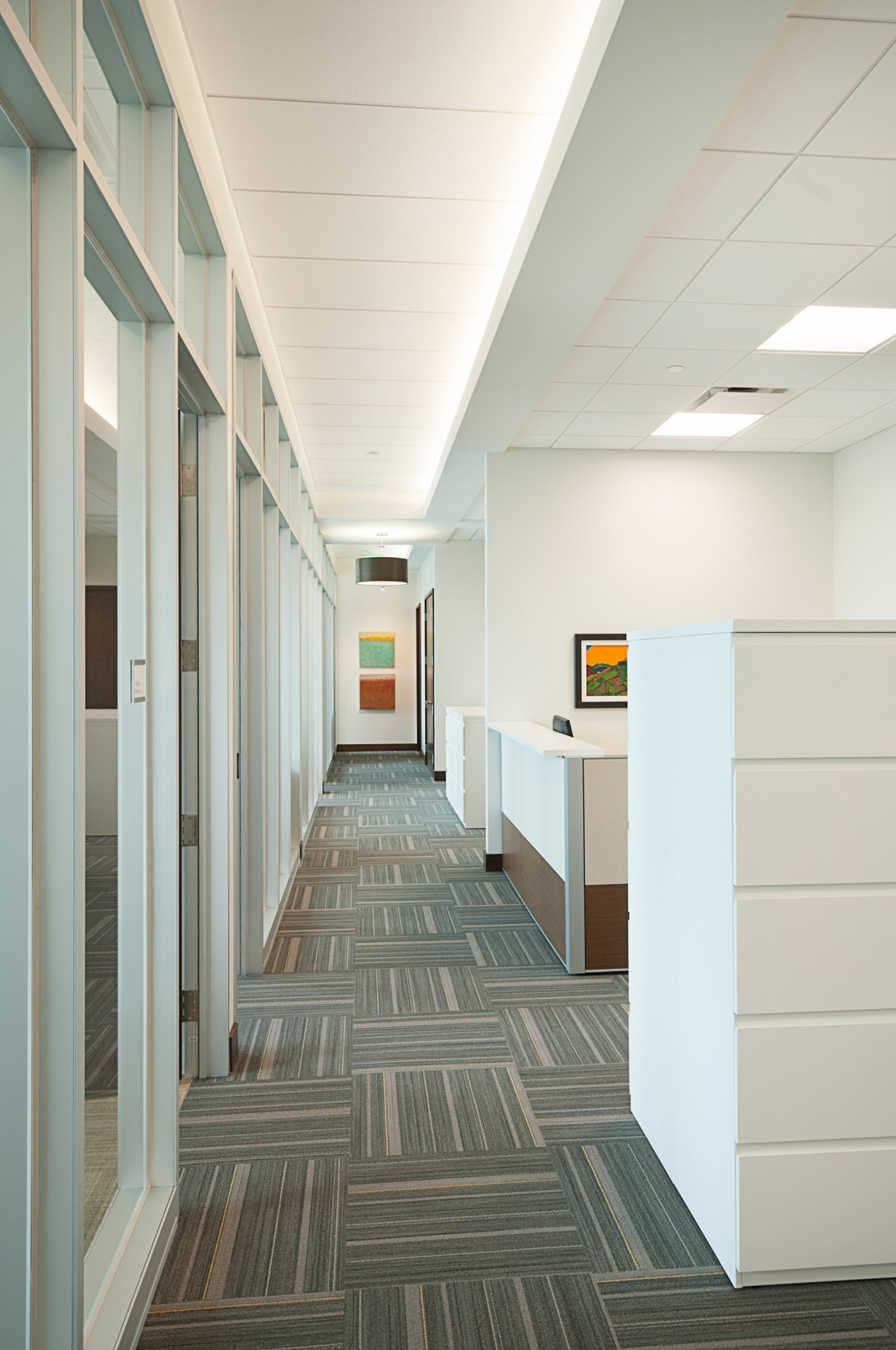 Typical circulation with glass office walls and indirect lighting.