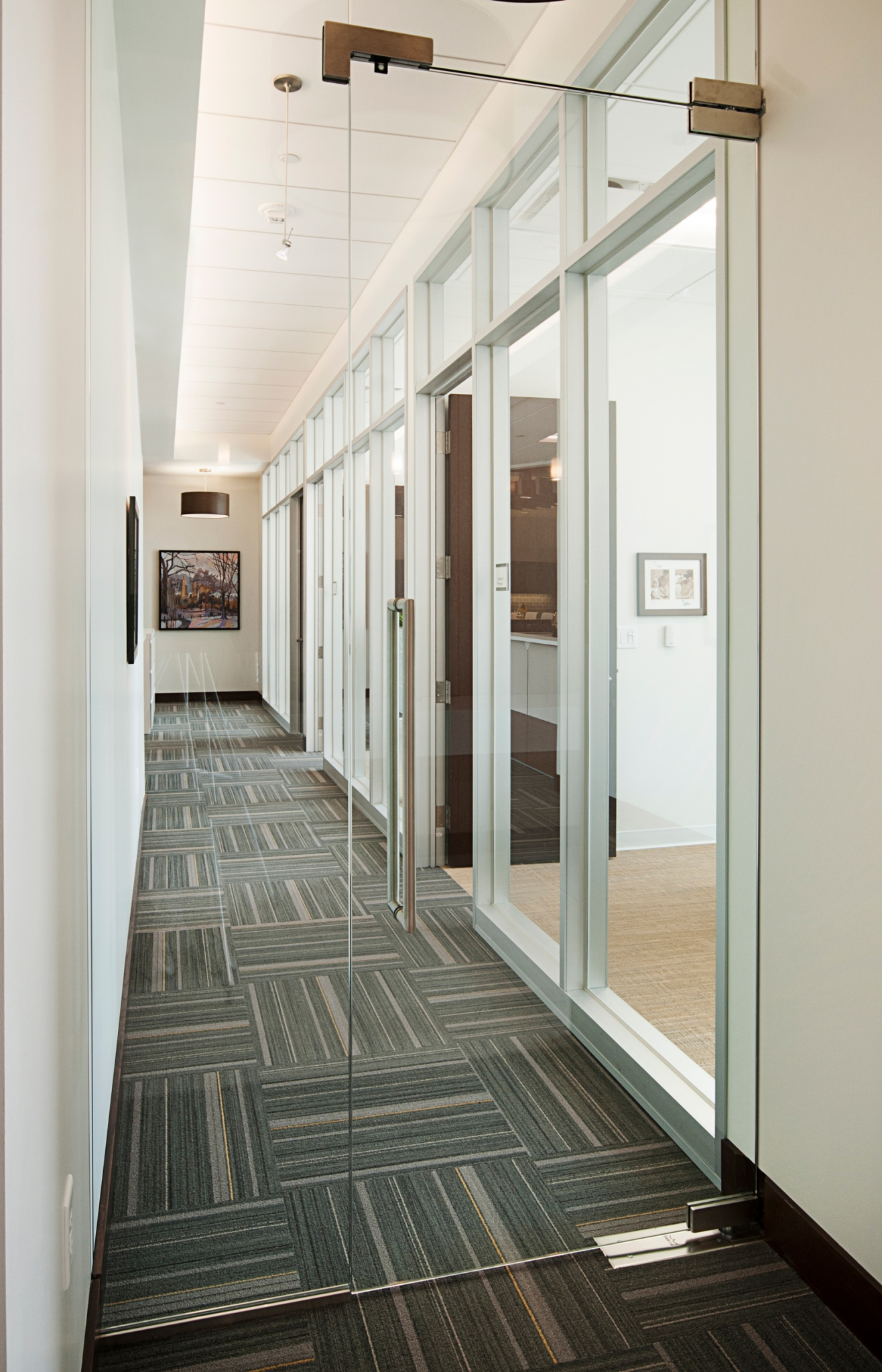 """Frameless glass door separating main conference room """"gallery"""" area from private offices."""